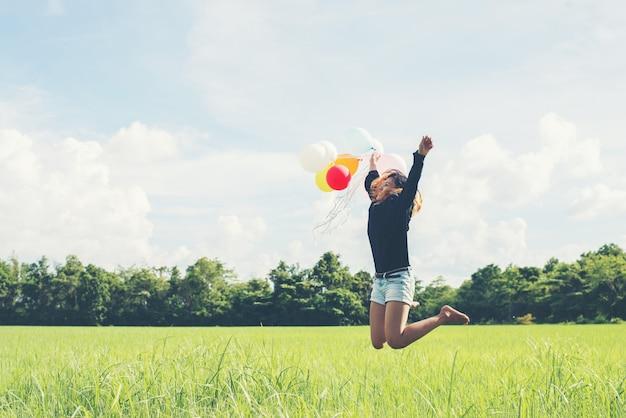 La ragazza che salta con palloncini sul greenfield