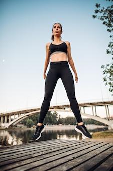 La ragazza che salta sulla piattaforma di legno sulla costa del fiume