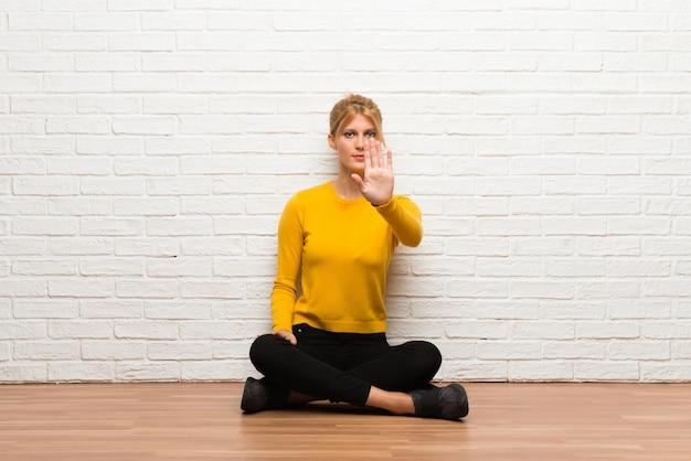 La ragazza che si siede sul pavimento che fa il gesto di arresto che nega una situazione che pensa sbagliato