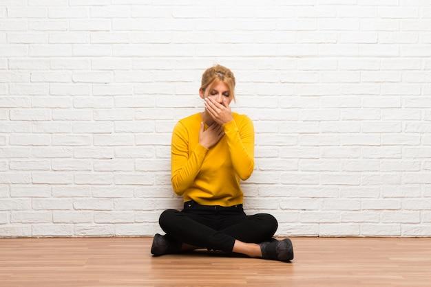 La ragazza che si siede sul pavimento sta soffrendo con la tosse e ritenendo cattiva
