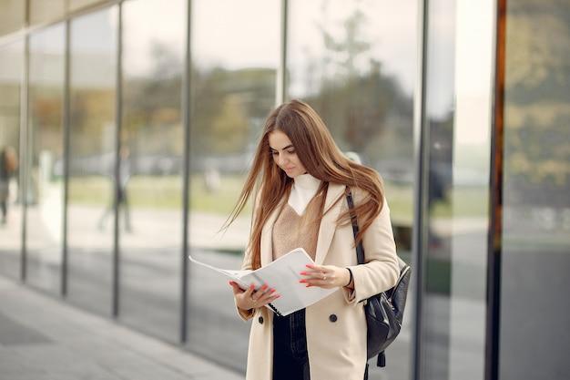La ragazza che sta in una città della molla e tiene i documenti in sua mano