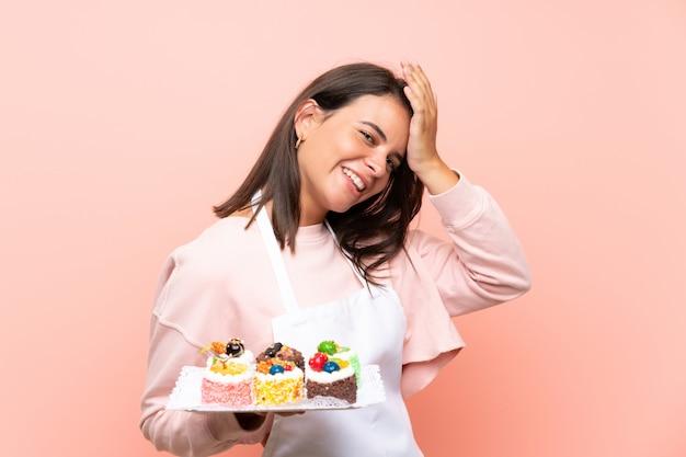 La ragazza che tiene un sacco di mini torte diverse sul muro isolato ha realizzato qualcosa