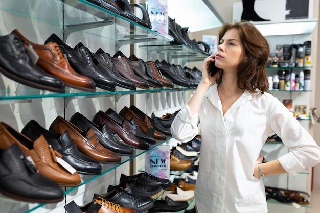 La ragazza chiama e consiglia per l'acquisto di scarpe da uomo.