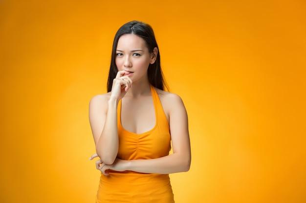 La ragazza cinese di pensiero su sfondo giallo