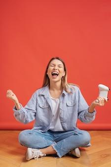 La ragazza competitiva celebra il regolatore di conquista del joystick del gioco della tenuta sulla parete rossa.