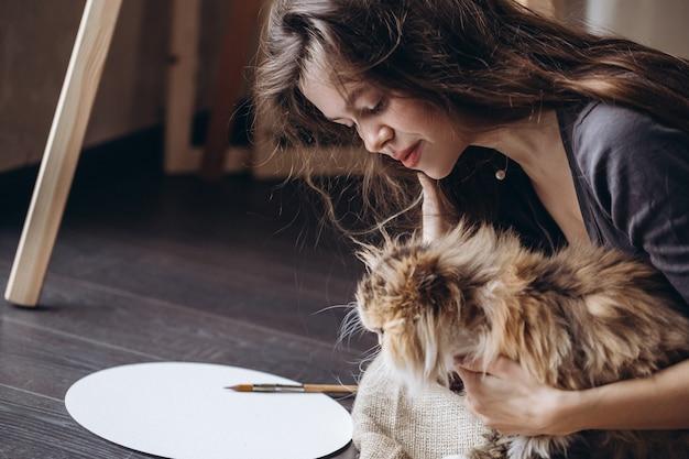 La ragazza comunica con il suo gatto birichino rosso domestico