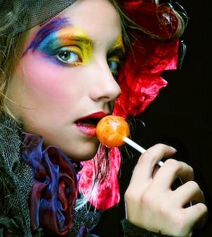 La ragazza con con trucco creativo tiene la lecca-lecca