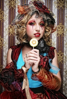La ragazza con con trucco creativo tiene la lecca-lecca.