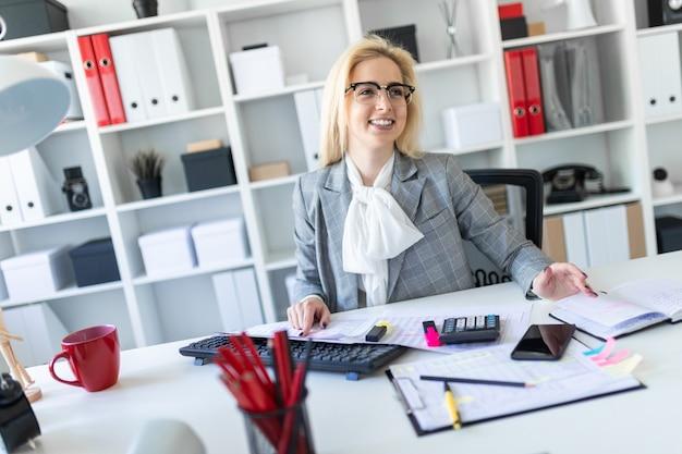 La ragazza con gli occhiali lavora in ufficio con documenti, calcolatrice e computer.