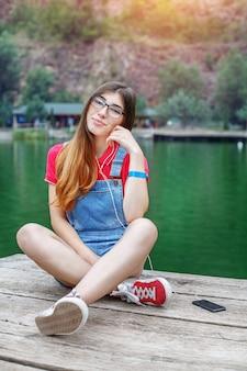 La ragazza con gli occhiali si siede sul lago. l'adolescente sta ascoltando la radio. stile di vita, viaggi, musica, riposo.
