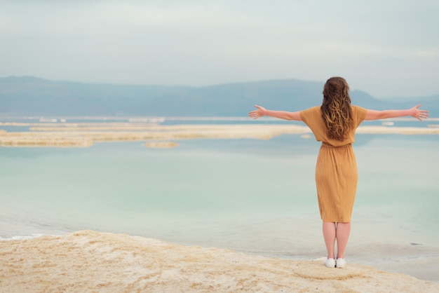 La ragazza con i capelli biondi brillanti va in riva al mare