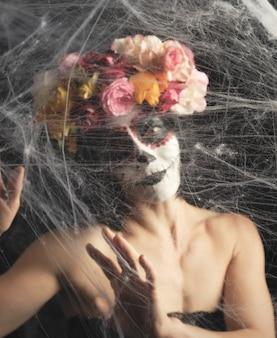 La ragazza con i capelli neri è vestita con una ghirlanda di rose colorate e il trucco è fatto sul suo viso cranio di zucchero