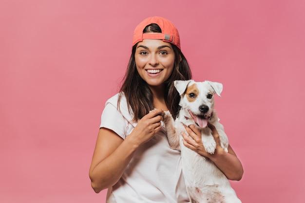 La ragazza con il berretto da baseball arancione, con indosso una maglietta rosa e jeans, tiene il cane per la zampa seduta in grembo, sorridendo ampiamente con gli occhi sorpresi aperti sul muro rosa. felicità e sogni.