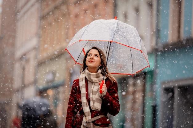 La ragazza con la caduta di neve bianca dell'ombrello resta sulla via della città