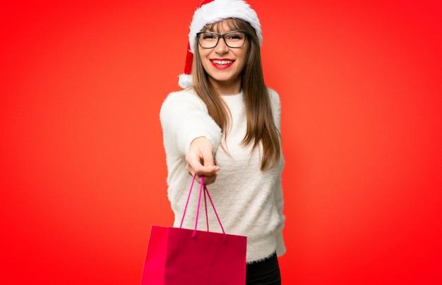 La ragazza con la celebrazione delle feste di natale ha sorpreso mentre teneva molto sacchetto della spesa