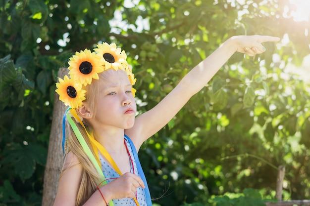 La ragazza con la decorazione di fiori sulla sua testa fa una faccia buffa.
