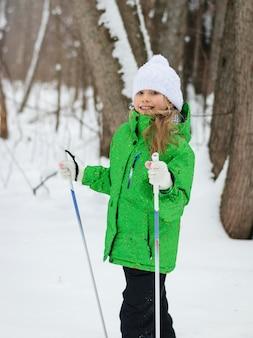 La ragazza con la giacca verde è appoggiata su un bastoncino da sci nel bosco
