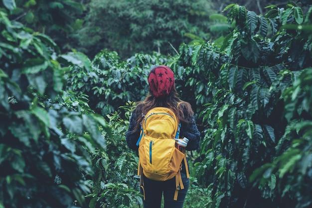La ragazza con lo zaino è in piedi e cammina nel giardino del caffè. il viaggio si rilassa