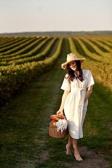 La ragazza con un cestino cammina sul campo.