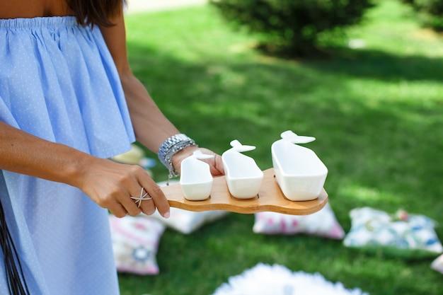 La ragazza con un set di salsiere vuote bianche su un vassoio di legno serve un picnic.