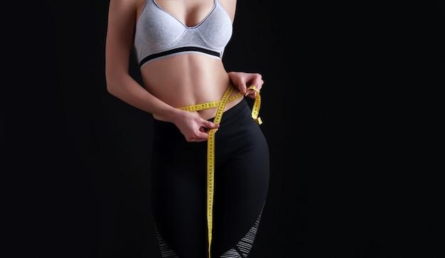 La ragazza con una figura sportiva perfetta misura le dimensioni della vita