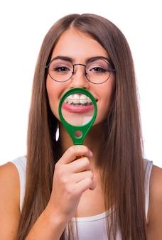 La ragazza con una lente d'ingrandimento tiene vicino ai denti.