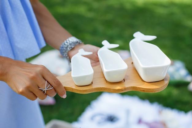 La ragazza con una serie di salsaboats vuote bianche su un vassoio di legno serve un picnic