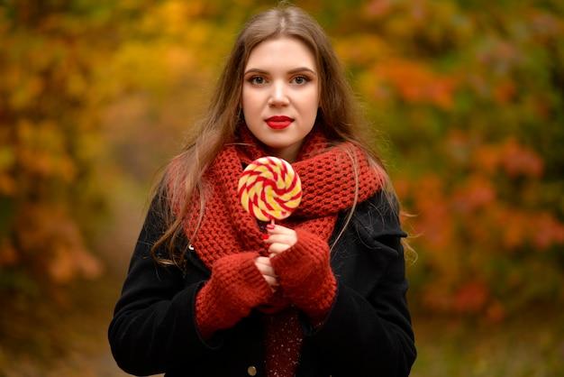 La ragazza con uno zaino e caramelle a piedi nel parco in autunno e sognare.