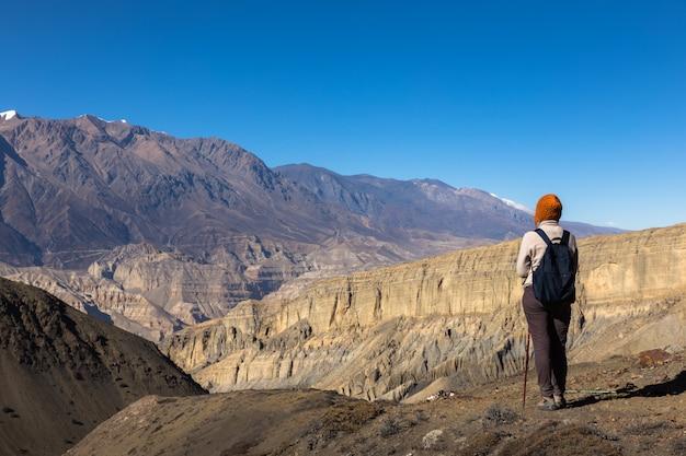 La ragazza con uno zaino esamina le montagne