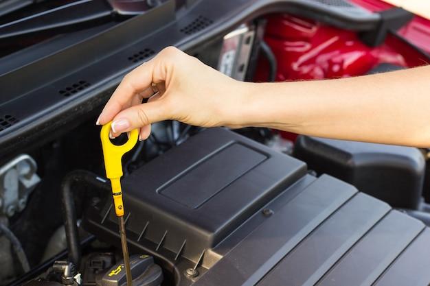 La ragazza controlla il livello dell'olio nell'auto, il concetto del problema sulla strada