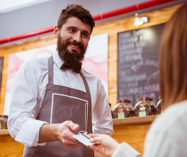La ragazza dà al venditore una carta di credito per pagare il conto.