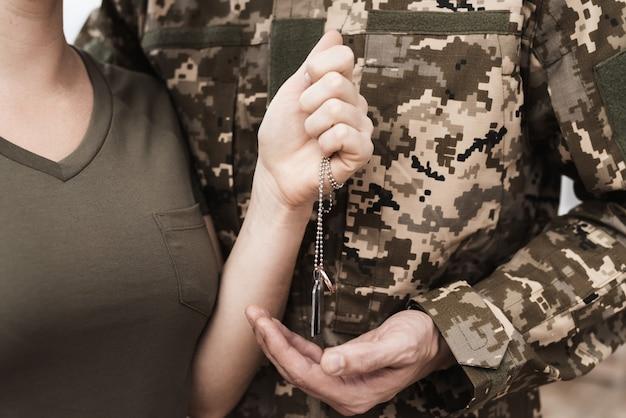 La ragazza dà il ciondolo a suo marito che va in guerra.