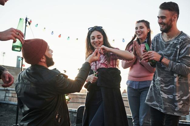 La ragazza dà il mignolo. dichiarazione d'amore sul tetto con compagnia di amici