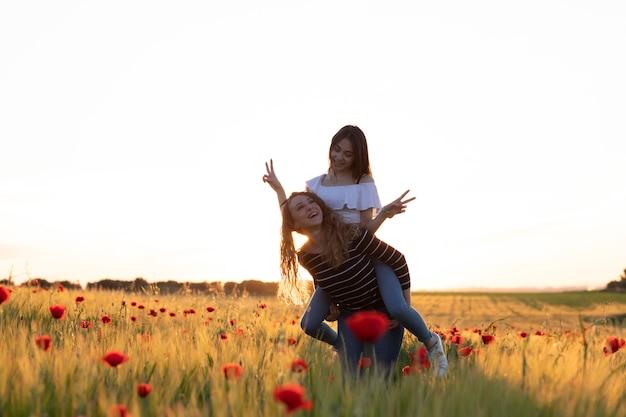 La ragazza dà un grande abbraccio e si arrampica sulla schiena della sua amica in una giornata molto felice.