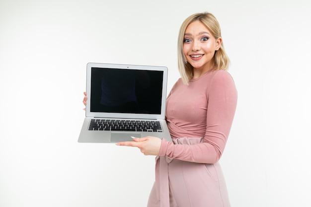La ragazza dai capelli corti con i capelli bianchi mostra uno schermo portatile con uno spazio vuoto su uno sfondo bianco studio