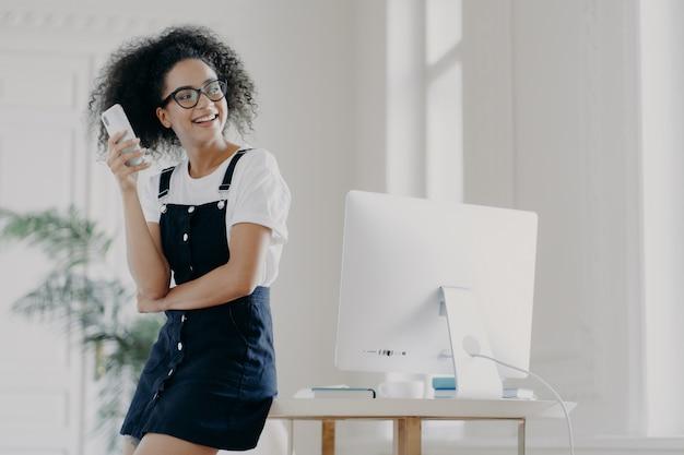 La ragazza dai capelli ricci felice utilizza il telefono cellulare per la comunicazione