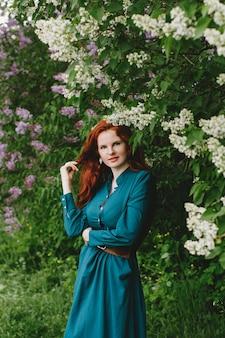 La ragazza dai capelli rossi è in piedi vicino al cespuglio di lillà