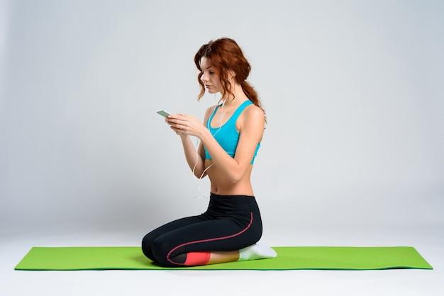 La ragazza dai capelli rossi si siede in grembo e applaude al telefono.