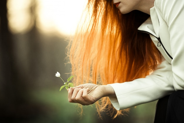 La ragazza dai capelli rossi sta ammirando il fiore