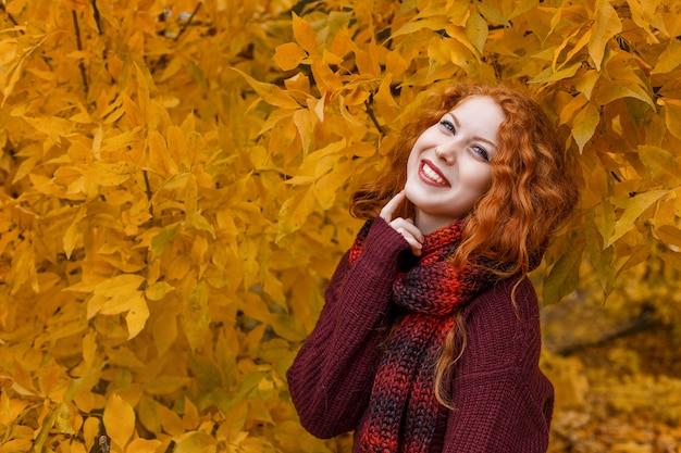La ragazza dai capelli rossi sveglia con un albero di autunno con una foglia in sua mano sorride e fa smorfie