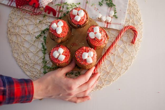 La ragazza decora i bigné di celebrazione di nuovo anno, muffin al cioccolato sul tavolo
