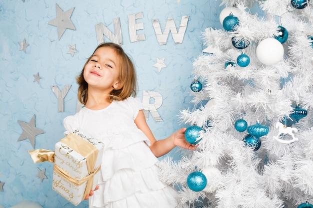 La ragazza decora le palle e sorridere dell'albero di natale