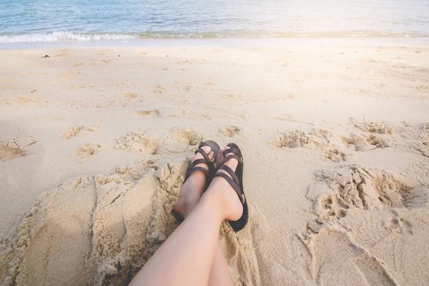 La ragazza dei piedi della donna si siede e rilassandosi sulla spiaggia.