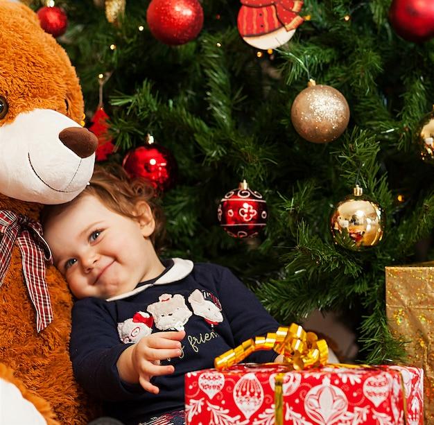 La ragazza del bambino con i regali si avvicina all'albero di natale.