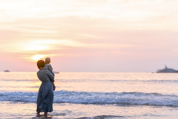 La ragazza del bambino e della donna sta nel mare in vestiti blu e gode del tramonto. calma familiare.