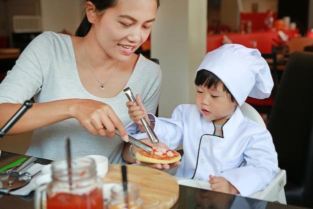 La ragazza del bambino e della madre in un vestito del piccolo cuoco unico realizza la mini pizza, cucinando il concetto del bambino.