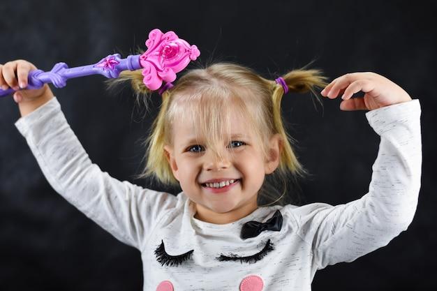 La ragazza del bambino evoca una bacchetta magica su sfondo nero