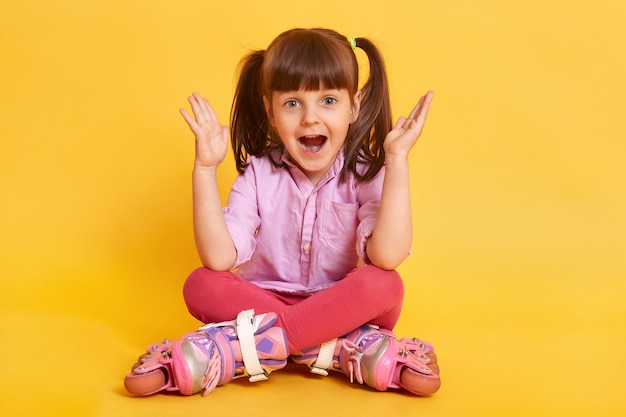 La ragazza del bambino nei pattini di rullo si siede sul pavimento a testo libero