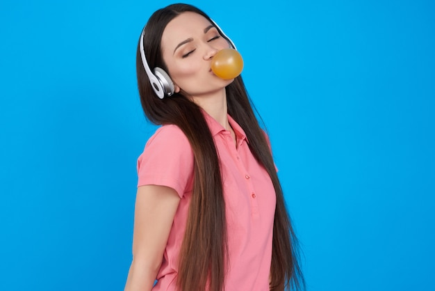 La ragazza del brunette propone con gomma da masticare isolata.