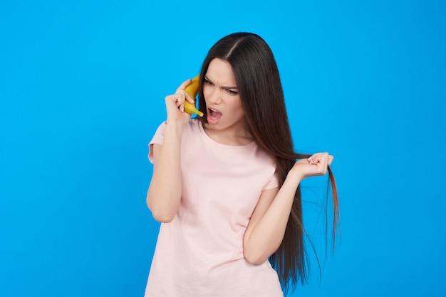 La ragazza del brunette propone con la banana isolata sul blu